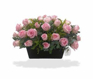 Arreglo floral con rosas rosas de llegale con flores